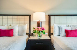Two queen bed room with night stand in between the two beds with a floral arrangement