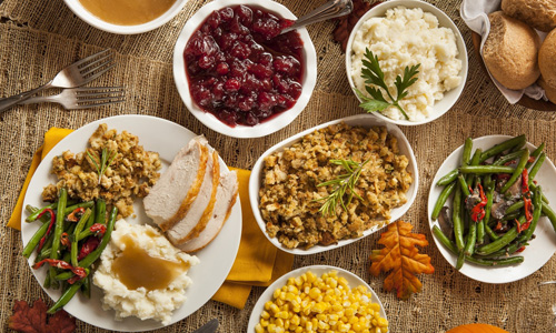 spread of thanksgiving dishes on a table including turkey, mashed potatoes, stuffing, cranberry, corn and green beans