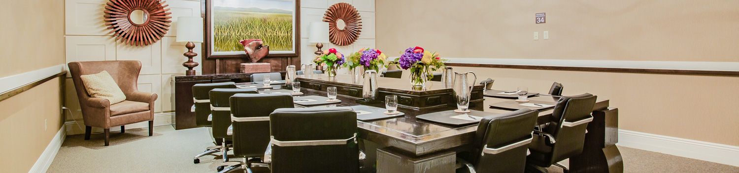 conference room with large table  with floral centerpieces surrounded by chairs