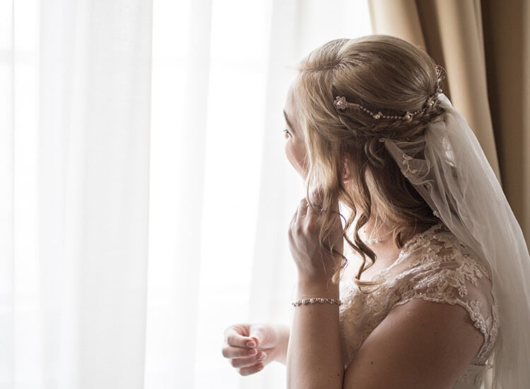 woman putting earrings on before her wedding