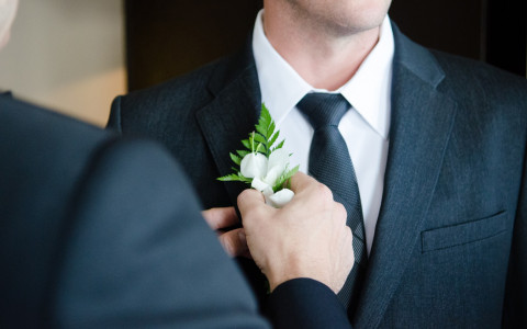 man tying his tie before his wedding