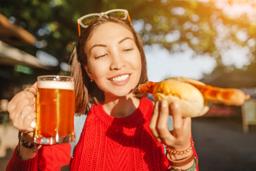 traveler woman drinks mug of beer with hotdog