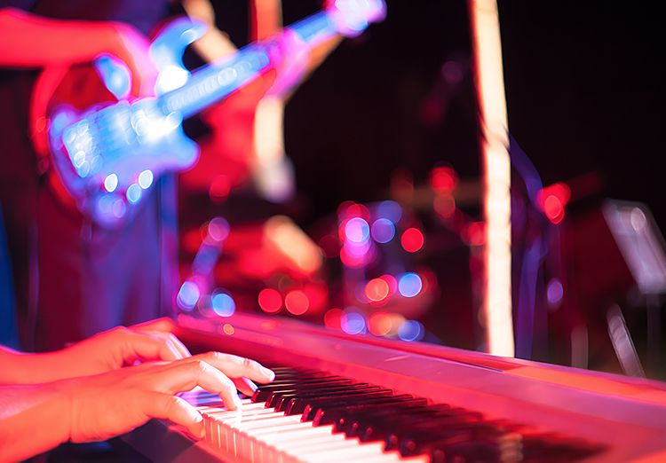 Close up of hands playing piano during concert with guitar player in the back