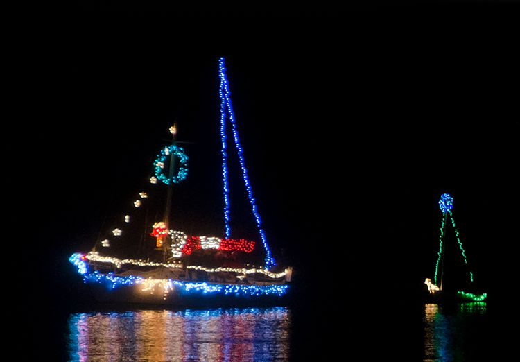 Sail boats on water lit up with Christmas lights