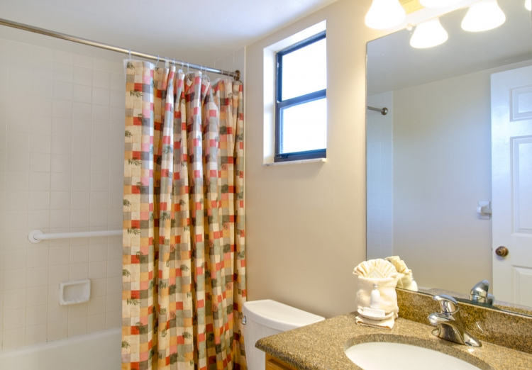 Full bathroom with granite countertop & shower with brightly patterned curtain