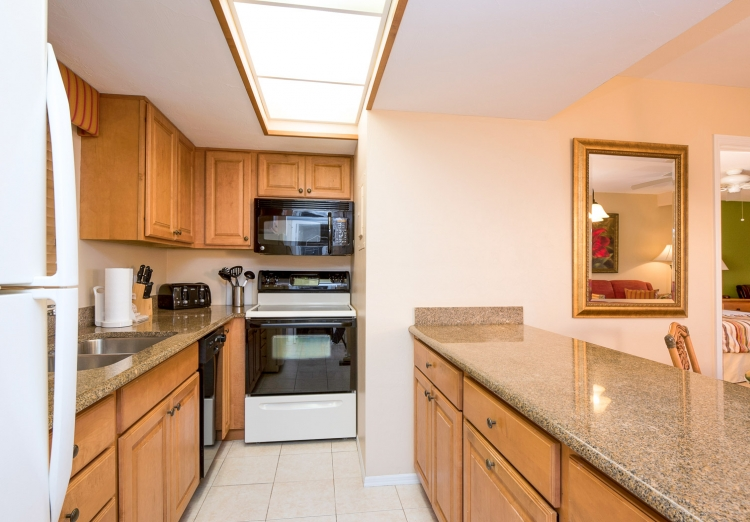 Full kitchen with granite countertops, wooden cabinets & appliances