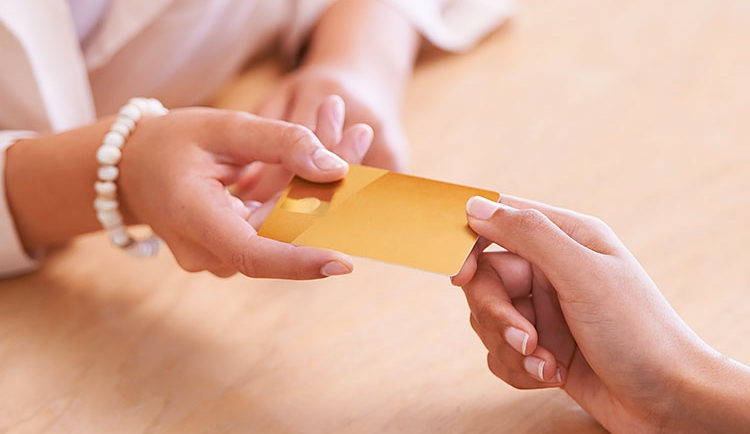 Close up of hand giving credit card to someone else