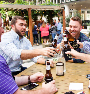 Group of men sitting at outdoor table toasting with beer