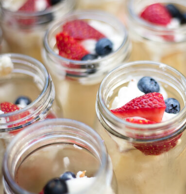 Close up of dessert in mason jars topped with fruit