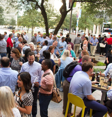 Crowd of people enjoying outdoor restaurant during happy hour
