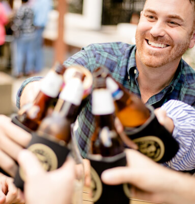 Close up of man toasting friends with beer bottles