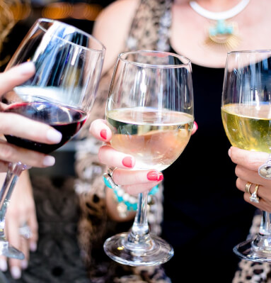 Close up of women holding three wine glasses