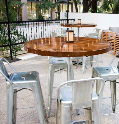Outdoor wooden tables with metallic chairs