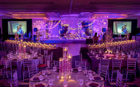 Venue glowing with purple lighting and tables full of tealights