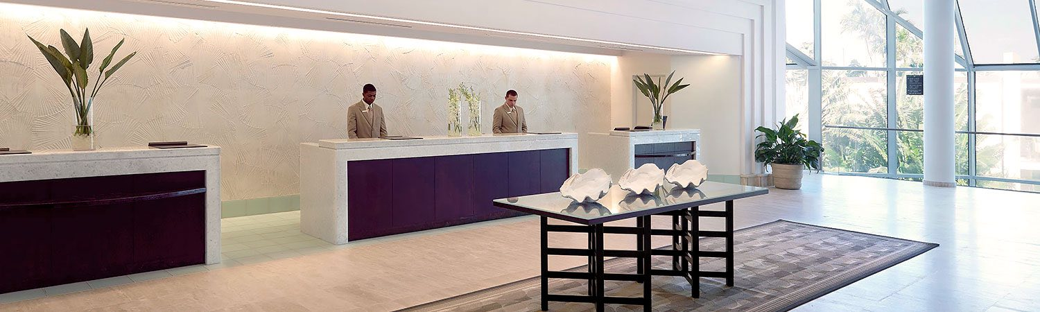 Minimalistic hotel lobby with wooden table & two staff members at front desk