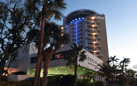 Hotel building lit up at dusk surrounded by palm trees
