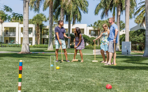 Friends playing croquet outside