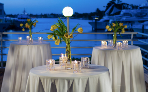 Small round tables with white tablecloths & yellow flowers set on outdoor terrace