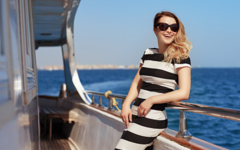 Woman wearing sunglasses & standing on yacht