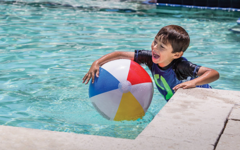 Small boy playing with beach ball in swimming pool
