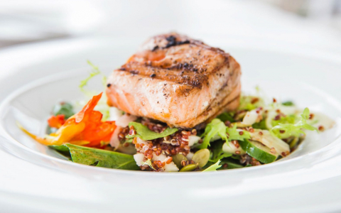 Grilled salmon on top of green salad