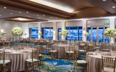 Panoramic view event space with round tables set for meal with tall vases & white roses