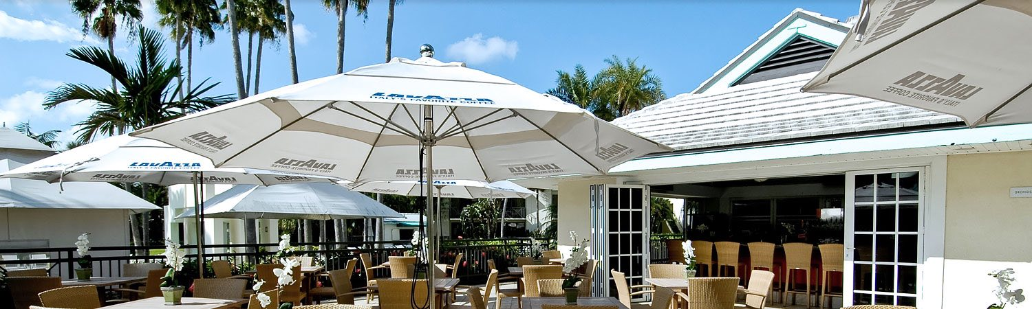 Outdoor patio tables and chairs set up under white umbrellas