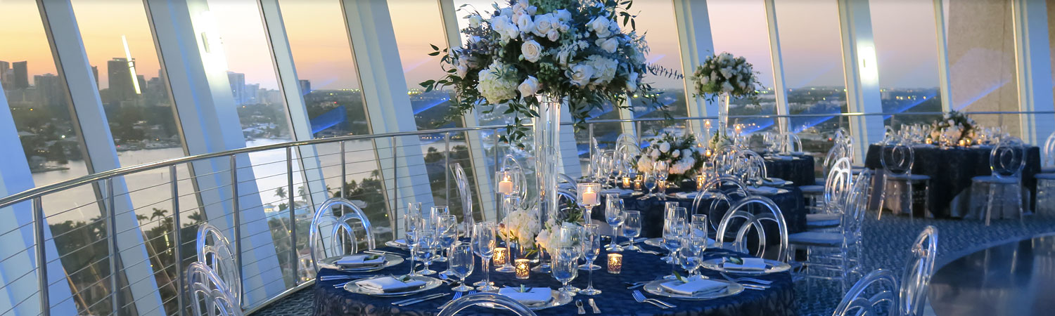Room set for wedding reception with round tables & large window panels overlooking ocean