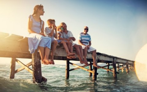 family sitting on pier by the sea stock photo
