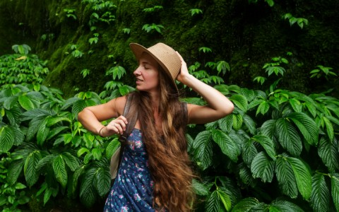 woman with hat in tropical forest