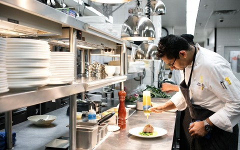 the chef plating a dish on the line