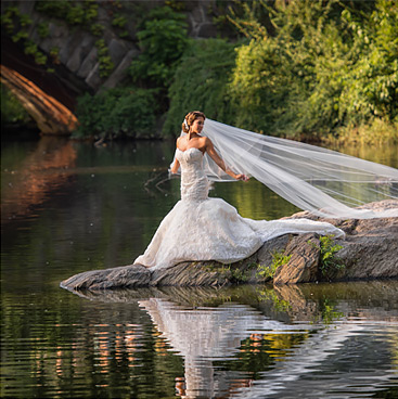 bride posing in front of water