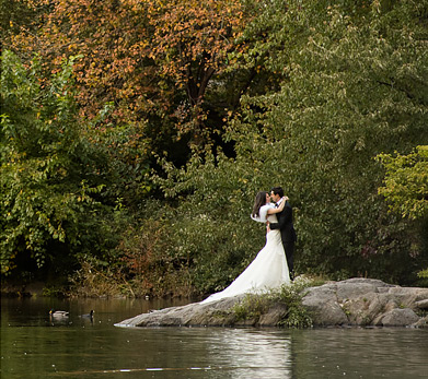 bride and groom posing by water