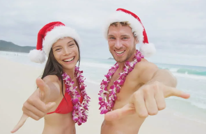 a man and a woman on the beach wearing santa hats
