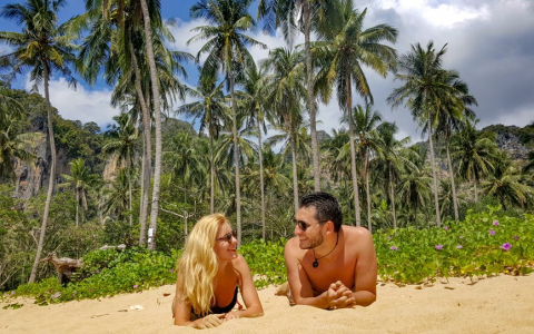 Couple Relaxing on Sunny Beach with Palms in the Background