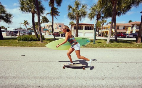 girl on skateboard holding surfboard
