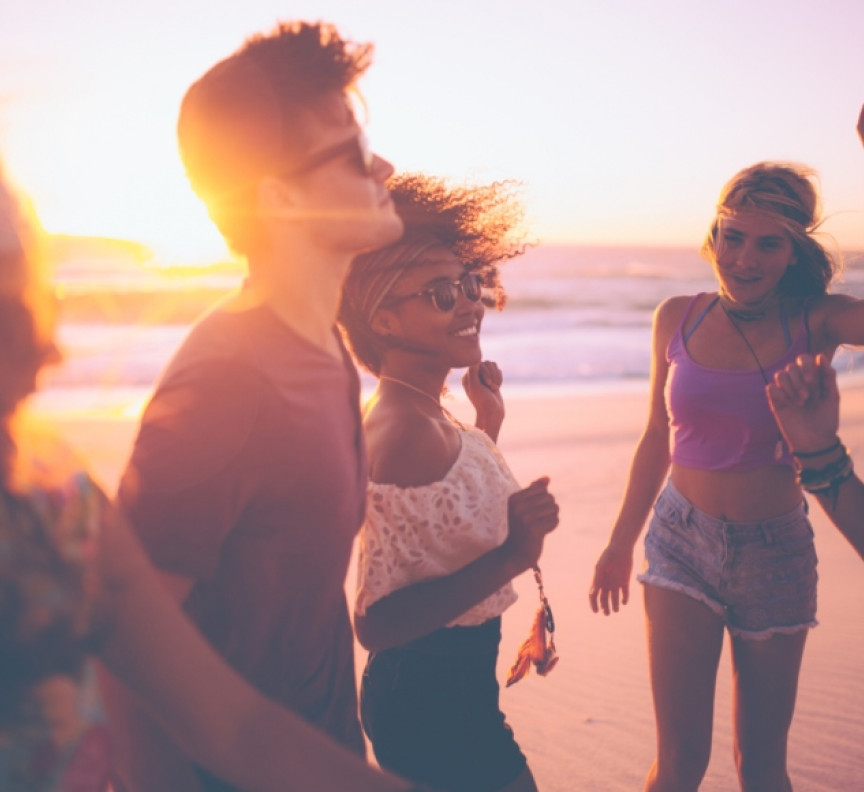 group of friends dancing together at a beachparty