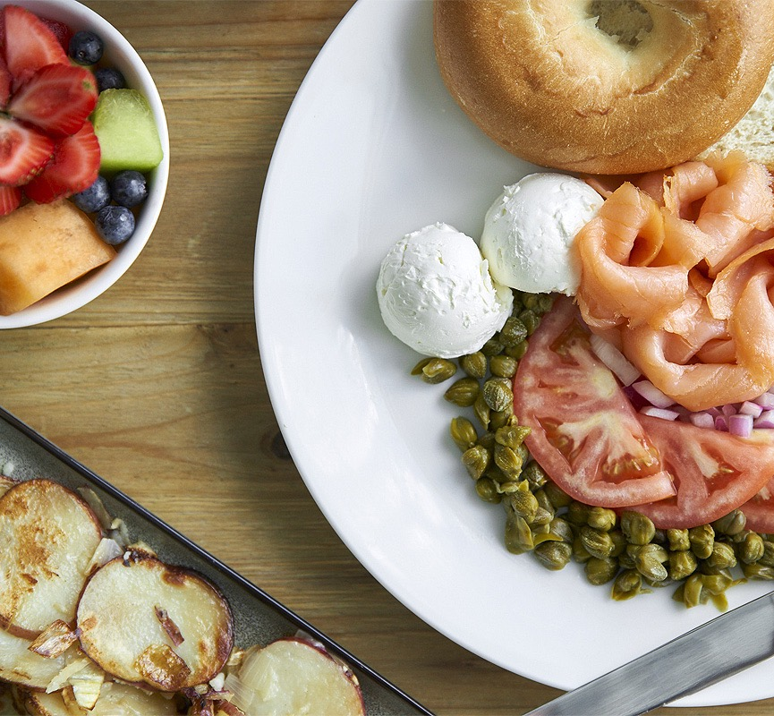 bagel on plate with cream cheese, lox, tomatoes, capers, and a bowl of fruit on side