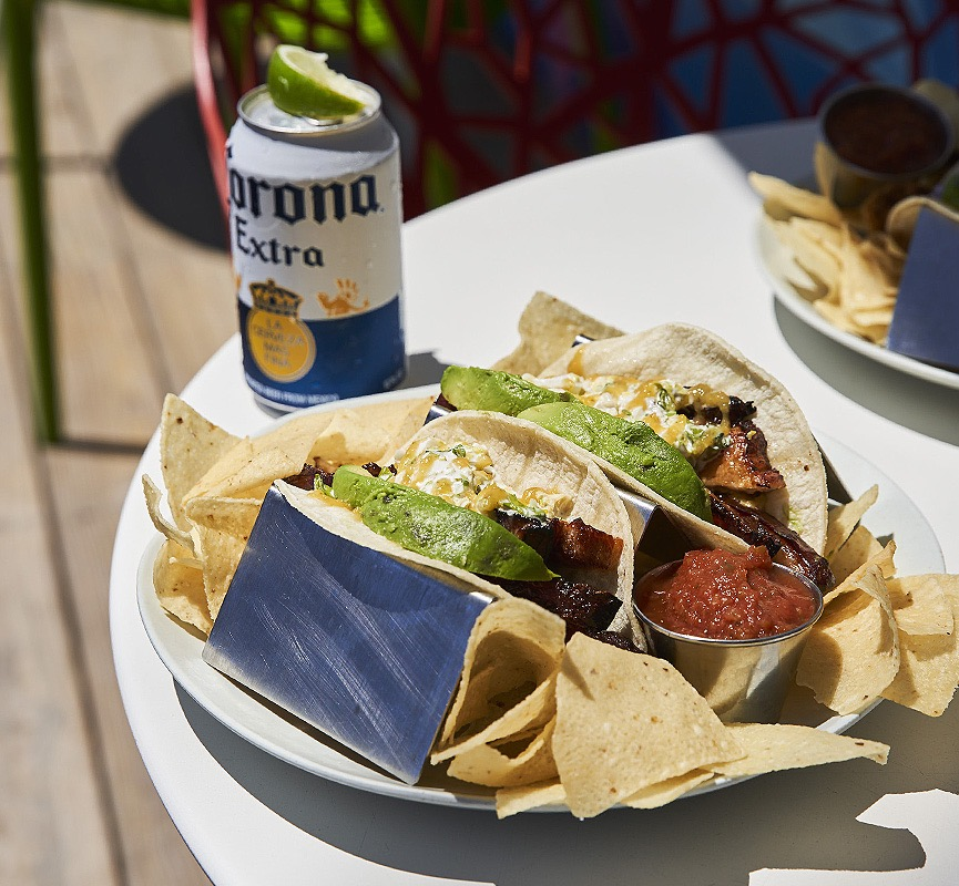 two tacos on plate with chips and a can of corona on the side