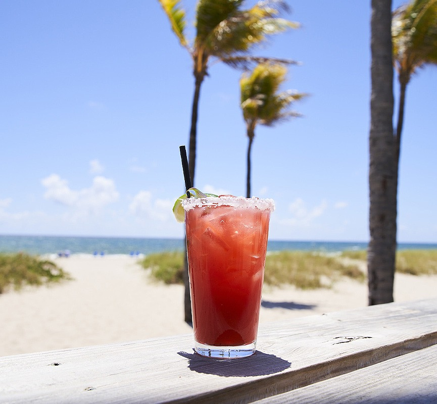 red colored cocktail on ledge facing beach