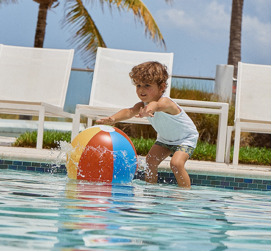 young boy reaching for beach ball in pool