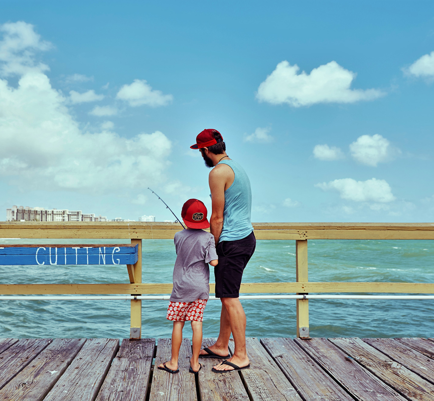 father and son fishing on dock