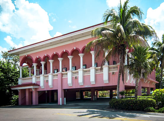 Pink building with white columns next to palm trees
