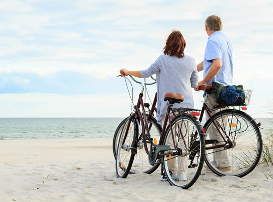 Couple standing with bikes on sand looking at the ocean