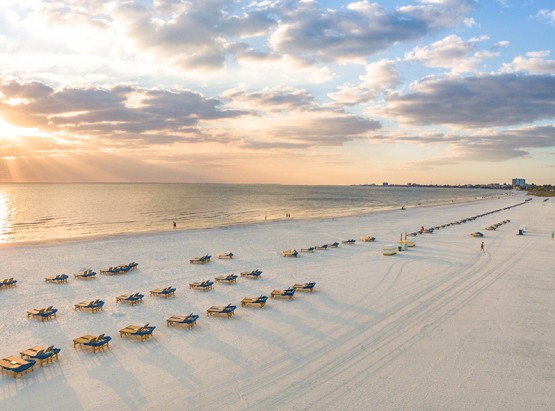 Rows of beach loungers on sand overlooking sunsetting on ocean