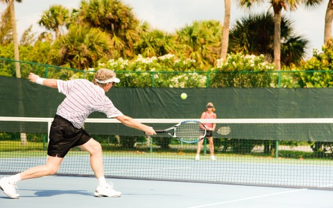 Couple playing tennis on court