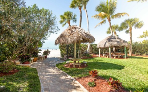 Brick path toward beach with tiki huts & palm trees