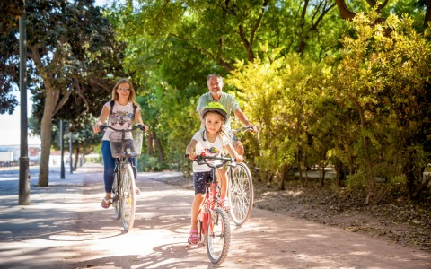 Couple & daughter riding bikes on path surrounded by trees
