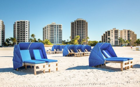 Blue loungers with umbrellas on sand with buildings in the back