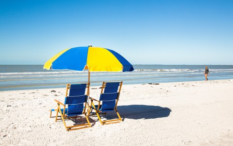 Two blue beach chairs with blue & yellow umbrella overlooking ocean